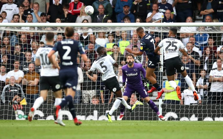 player rises to score one of four goals by leeds at derby
